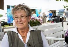 Alte lächelnde Frau im Café Stockfotos