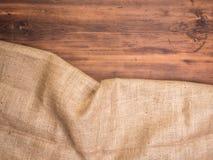 Alte ländliche Holztischbretter und Leinwandweinlesehintergrund, Draufsicht des Fotos Grobes Sackzeug, Rausschmissbeschaffenheit  Lizenzfreie Stockfotografie