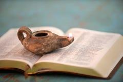 Alte Öl-Lampe auf offener Bibel Stockbilder