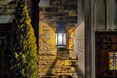 Alte Lampe auf einer Steinwand Stockfotos