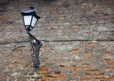 Alte Lampe auf einer strukturierten Backsteinmauer stockfoto
