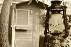 Alte Lampe in der Tür einer hölzernen Hütte stockfotografie