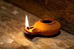 Alte Lampe des nahöstlichen Öls hergestellt im Lehm auf hölzerner Tabelle Stockfoto