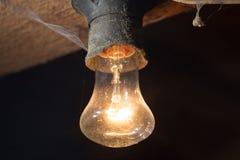 Alte Lampe, die auf einer hölzernen Decke brennt Lizenzfreies Stockfoto