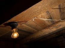 Alte Lampe, die auf einer hölzernen Decke brennt Stockbild