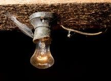 Alte Lampe, die auf einer hölzernen Decke brennt Stockbilder