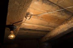 Alte Lampe, die auf einer hölzernen Decke brennt Lizenzfreie Stockfotos