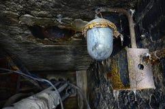 Alte Lampe, die von geschädigter Decke hängt Hammer auf zerbrochenem Glas mit Splittern Lizenzfreie Stockbilder