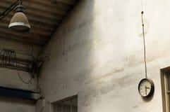 Alte Lampe und Wand mit industrieller Uhr Stockfoto