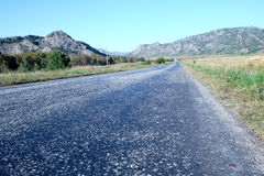 Alte Landstraße gegen Berge Lizenzfreie Stockfotos