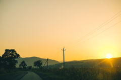 Alte Landstraße gegen Berge und einen bewölkten Himmel Lizenzfreie Stockfotografie