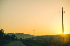 Alte Landstraße gegen Berge und einen bewölkten Himmel Stockfotografie