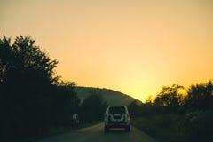 Alte Landstraße gegen Berge und einen bewölkten Himmel Lizenzfreies Stockbild