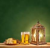 Alte Laterne mit Bier und Käse auf grünem Weinlesehintergrund Lizenzfreies Stockfoto