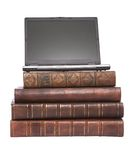 Alte lederne gebundene Bücher mit einem Laptop Stockbild