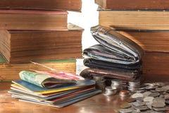 Alte lederne Geldbörsen und Sparbücher mit Münzen auf hölzernem Schmutz Lizenzfreie Stockbilder