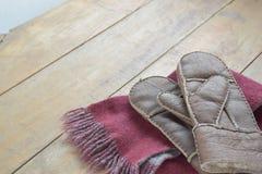 Alte lederne Handschuhe und Schal auf hölzerner Tabelle Lizenzfreie Stockfotografie