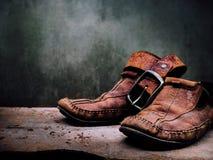 Alte Lederschuhe und Gurt des Stilllebens Es mehr von schmutzigem und von sha Stockbilder