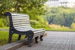 Alte leere Holzbank in einem Schatten des großen grünen Baums am hellen Sommertag Friedens-, Rest-, Ruhe- und Entspannungskonzept Stockfotografie