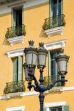 Alte Leuchten kontrastierten gegen alte gelbe französische Wohnungen Stockbilder
