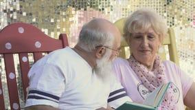 Alte Leute lesen Buch in den Schaukelstühlen, den Ehemannkuß eine Frau in einer Backe stock footage