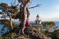 Alte Leute sitzen auf einem nahen weißen Steinleuchtturm, gelegen an der Küstenlinie von Portofino-Stadt, Italien Lizenzfreie Stockfotografie