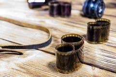 Alte Linse und Filme auf Holztisch Stockfotografie