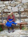 Alte lokale Frau, die auf einer Bank vor Steinwand auf der Straße der historischen Stadt und ethnographischer Reserve von Koprivs Stockbild
