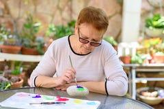 Alte ?ltere Frau, die den Spa? malend im Kunstunterricht im Freien hat lizenzfreie stockbilder