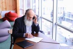 Alte Männer im Ruhestand nennen, um sich mit intelligentem Telefon unter Verwendung des neuen techn zusammenzutun Lizenzfreie Stockfotografie