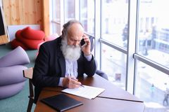 Alte Männer im Ruhestand nennen, um sich mit intelligentem Telefon unter Verwendung des neuen techn zusammenzutun Lizenzfreie Stockbilder