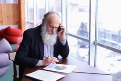 Alte Männer im Ruhestand nennen, um sich mit intelligentem Telefon unter Verwendung des neuen techn zusammenzutun Stockfoto