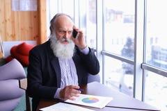 Alte Männer im Ruhestand nennen, um sich mit intelligentem Telefon unter Verwendung des neuen techn zusammenzutun Stockbild