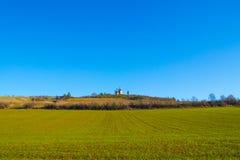 Alte Mühlen in den Tiefen eines grünen Feldes Lizenzfreies Stockfoto