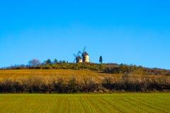 Alte Mühlen in den Tiefen eines grünen Feldes Stockfotografie
