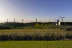 Alte Mühlen und moderne Luftturbinen gegen den Hintergrund einer ländlichen Landschaft Stockbild