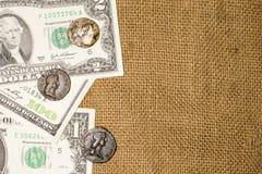 Alte Münzen und Dollarbanknoten über den Rausschmiß Stockfoto