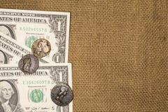 Alte Münzen und Dollarbanknoten über Sack Stockbild