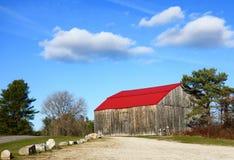 Alte Maine-Landscheune, helles rotes Dach, blauer Himmel Lizenzfreies Stockfoto