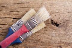 Alte Malerpinsel auf hölzernem Hintergrund Stockfotos