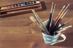 alte Malerpinsel in einem Becher oder in einer Schale mit Aquarell oder Watercolour Lizenzfreie Stockbilder