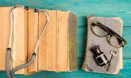 Alte medizinische Bücher mit Stethoskop, Gläsern, Flasche und Schlüssel auf b Lizenzfreies Stockbild