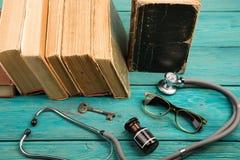 Alte medizinische Bücher mit Stethoskop, Gläsern, Flasche und Schlüssel auf b Lizenzfreie Stockfotos