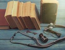 Alte medizinische Bücher mit Stethoskop, Gläsern, Flasche und Schlüssel auf b Stockfotografie
