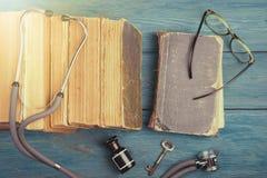 Alte medizinische Bücher mit Stethoskop, Gläsern, Flasche und Schlüssel auf b Stockfoto