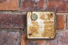 Alte metallische rote rostige Platte auf einer Backsteinmauer Stockbild