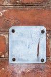 Alte metallische rote rostige Platte auf einer Backsteinmauer Stockfotos