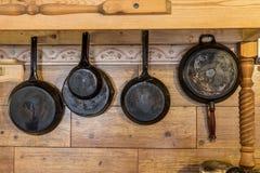 Alte metallische rustikale Wannen, die an der hölzernen Wand hängen Stockfoto