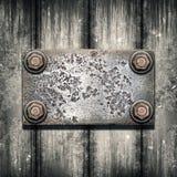 Alte Metallplatte auf metallischer Wand lizenzfreie stockfotos