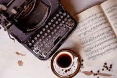 Alte Metallschreibmaschine, auf dem Tisch bedeckt im Staub und im rustCup des Kaffees Die Atmosphäre des Komforts und der Kreativ Lizenzfreie Stockfotos